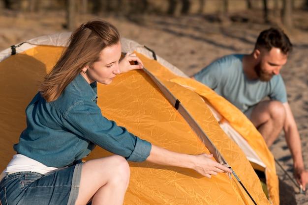 キャンプテントを解体するカップル