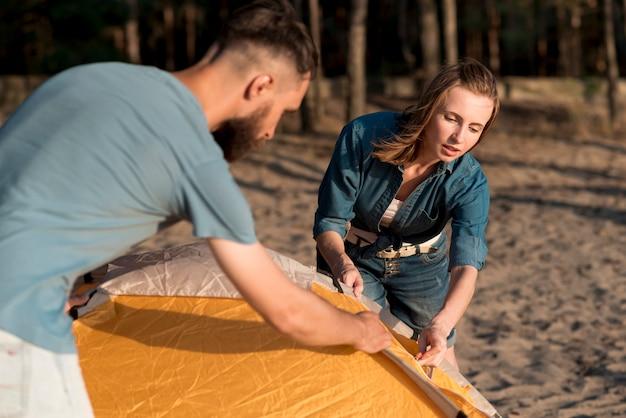 Пара помогает друг другу устанавливать палатку