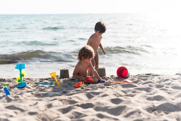 Братья и сестры делают замки на берегу моря