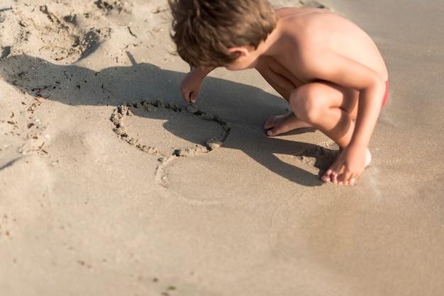 しゃがみ子供が砂で遊んで