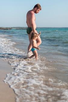 父と息子、水に向かって歩く