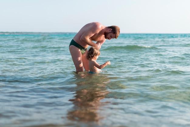父と息子、海で遊んで