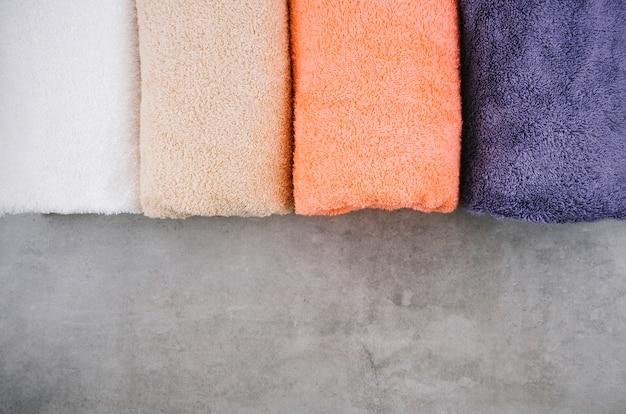 Вид сверху полотенца на сером фоне с копией пространства