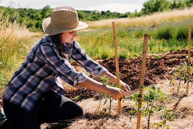 Женщина стоит на коленях и делает ставку в саду