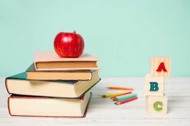 Вид спереди стопка книг и деревянный алфавит