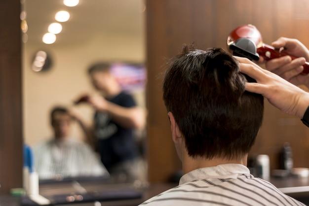 散髪を受ける背面図男