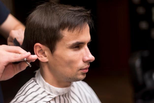 散髪を受ける男の横の肖像画を閉じる
