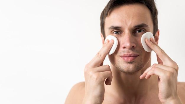 綿のディスクで顔を掃除する男の肖像