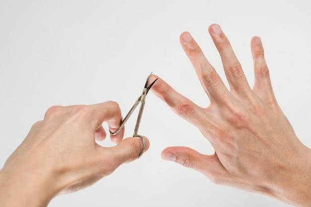 彼の爪を切る男のクローズアップ