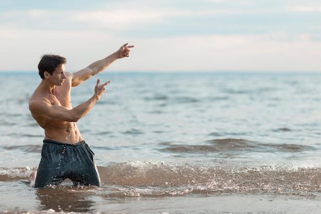Человек позирует в воде с копией пространства