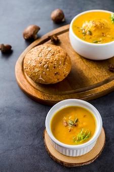 Взгляд высокого угла супа сквоша на деревянной доске