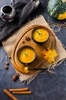 Взгляд высокого угла мисок супа сквоша на деревянной доске