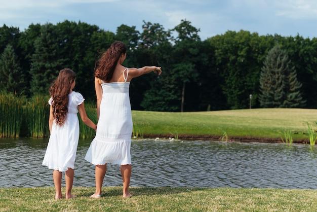 Вид сзади мать и дочь, глядя на озеро