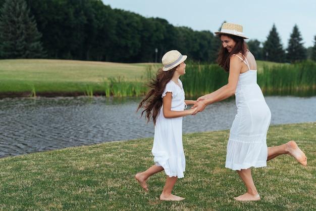 Мать и дочь танцуют на берегу озера
