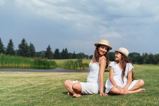 母と娘が自然の中で一緒に座っています。