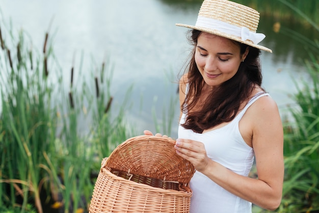 湖のそばのピクニックバスケットを持つ女性