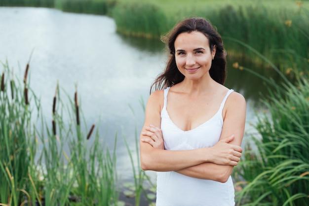 Красивая мать позирует на берегу озера