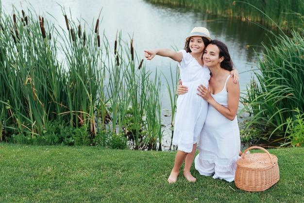 Счастливая мать и дочь позирует на берегу озера