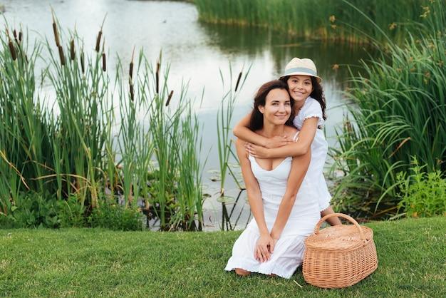 幸せな母と娘、湖のそばでポーズ