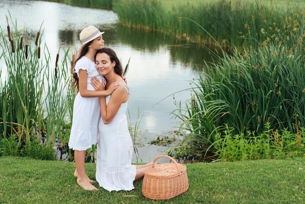 母と娘、湖のそばでハグ