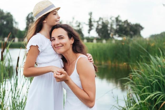 ミディアムショットの母と娘、湖のそばでハグ