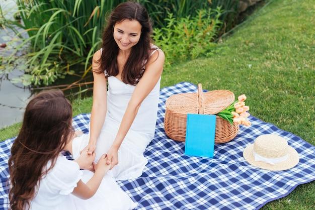 トップビューの母と娘のピクニックで手を繋いでいます。