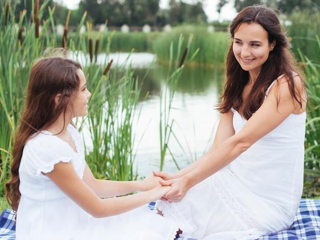 母と娘、湖のそばで手を繋いでいます。