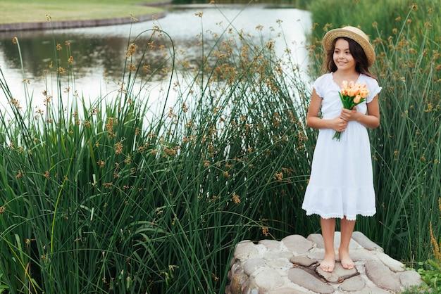 湖のそばで花を持ってかわいい女の子