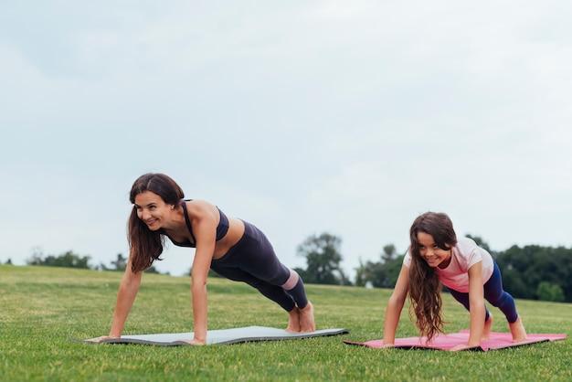 笑顔の母と娘が屋外で運動