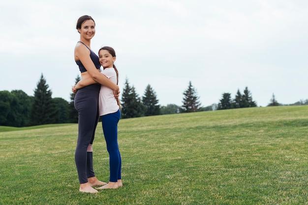 Боком мама и дочка обнимаются на природе