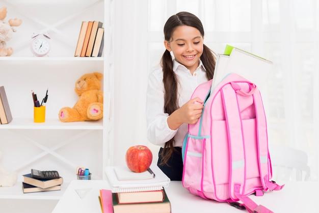 Радостная испанская школьница упаковывает школьную сумку
