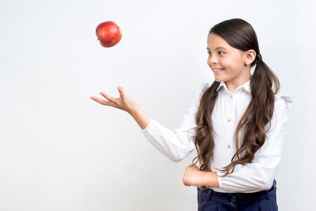 Игривая школьница испаноязычных подбрасывает яблоко