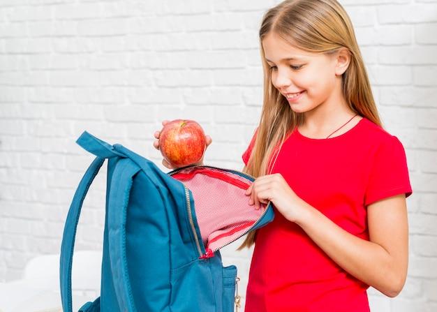 Счастливая девушка кладет яблоко в рюкзак