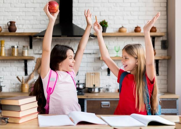 Школьницы с поднятыми руками, глядя друг на друга
