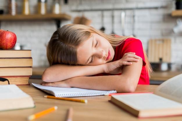宿題をしている間に疲れた女の子