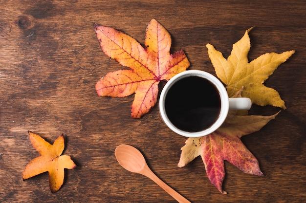 木製の背景に紅葉のコーヒーカップ