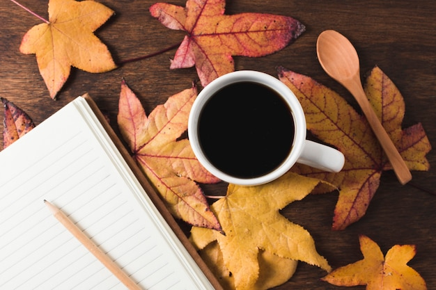コーヒーカップと秋のノートブックの葉の背景
