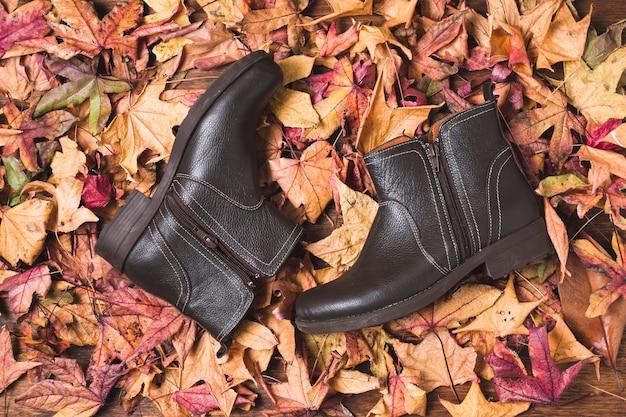 乾燥葉の背景にレザーブーツ