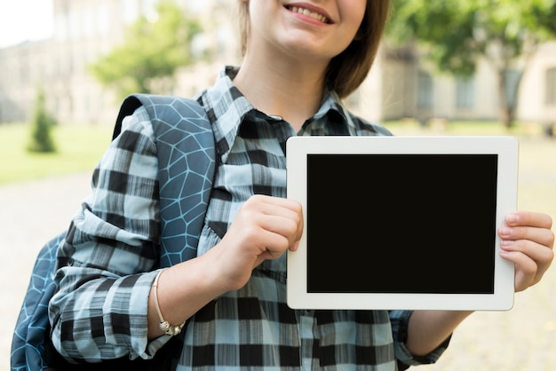 Крупным планом школьница, держа планшет
