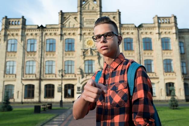 Средний снимок подростка, указывая на камеру