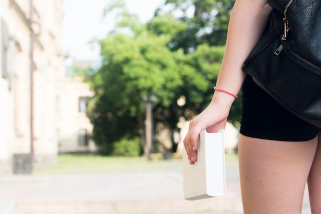 Крупным планом девушка держит книгу в руке