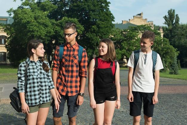 Средний снимок друзей-подростков, идущих в старшую школу