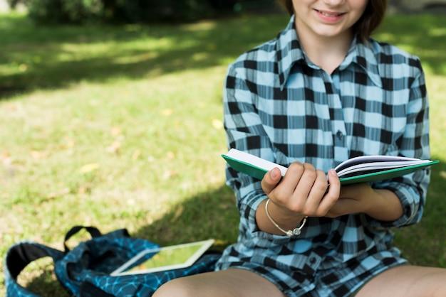 本を読んで座っている高校の女の子のクローズアップ
