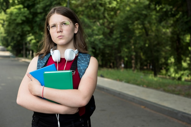 Средний снимок мечтательной старшеклассницы с книгами в руках