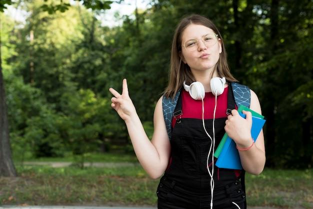 本を手に笑顔の高校の女の子のミディアムショット