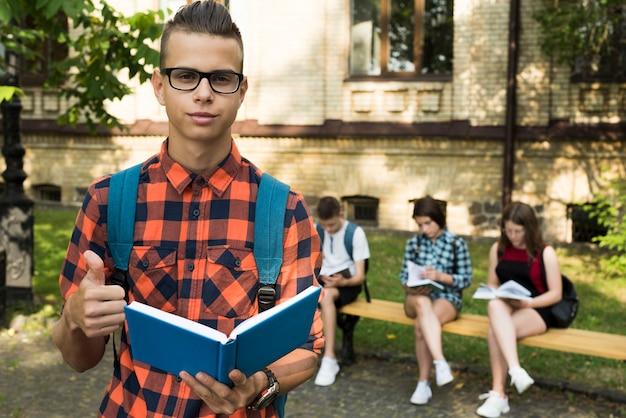 開いた本を保持している高校の男の子のミディアムショットの肖像画