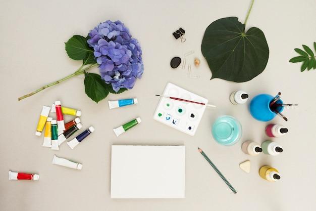 Акварель и кисти с эскизом на столе в художественной рабочей области