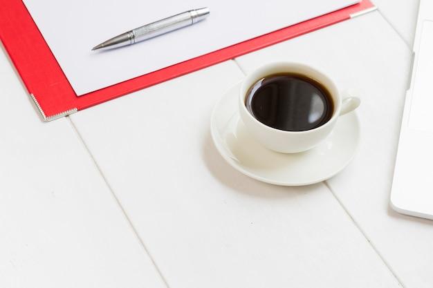 コーヒーのマグカップと机の上のドキュメントの職場事務所