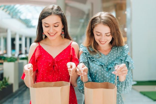 Средний снимок улыбающихся девушек, заглядывающих в сумки