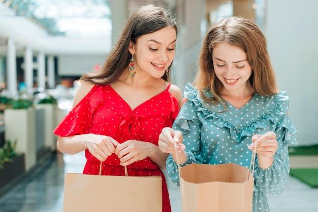 彼女の友人の買い物袋をチェックする女性